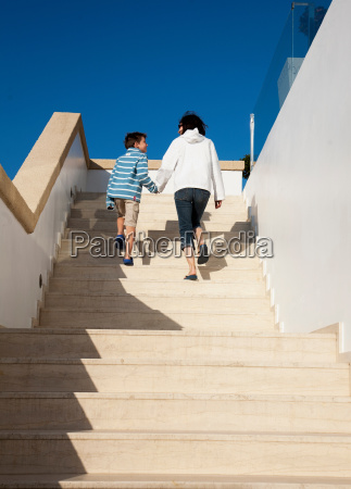 mother and son walking up steps