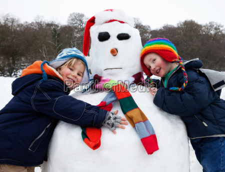 two boys hugging a snowman