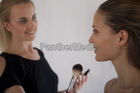 makeup artist applying blush to model