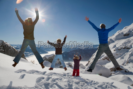 happy family jumps in winter mountains