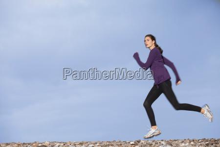 woman jogging along pebble beach