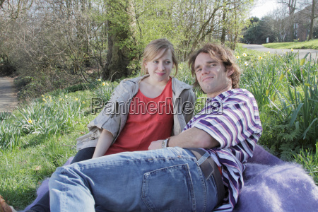 couple laying on blanket in park