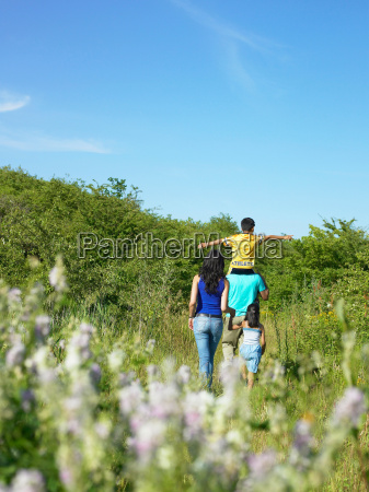 family walking in field of flowers