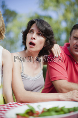surprised woman sitting at picnic table