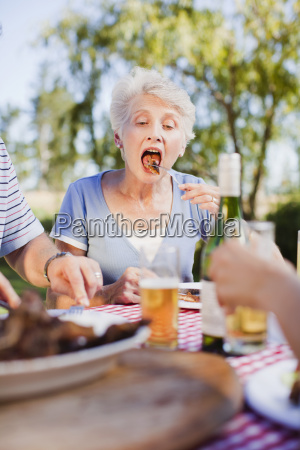 older woman eating at picnic table