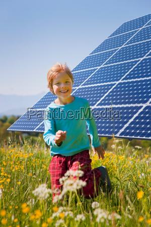 boy playing in field by solar