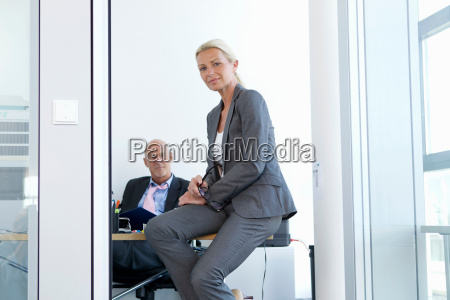 businesswoman sitting on desk in office