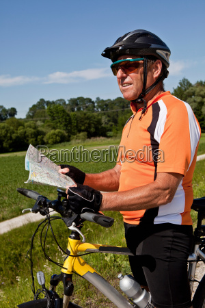 biker reading map on rural road