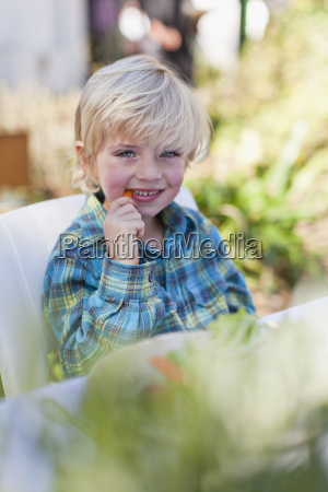 boy eating at table outdoors