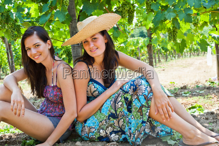 smiling women sitting by tree in