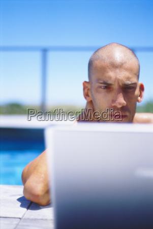 man using laptop in swimming pool