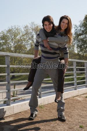 man piggybacking woman outdoors smiling