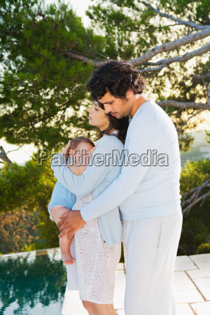 family w baby embracing in nature