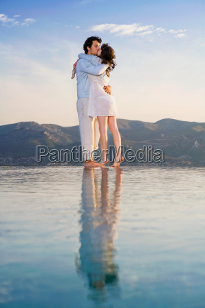couple kissing by infinity pool