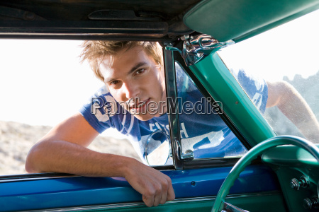 man leaning into car