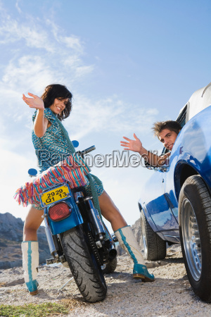 man in car woman on motorbike