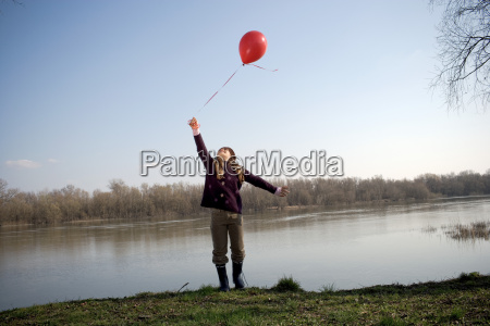 girl by river holding red balloon