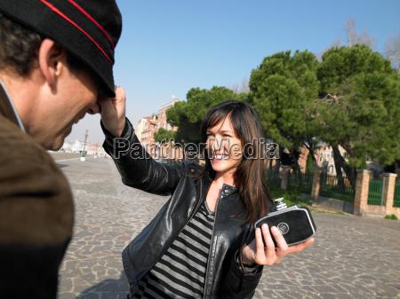 woman taking photograph of man