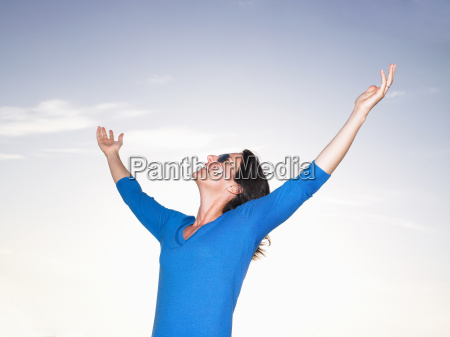 woman stretching her arms blue sky