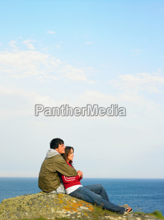 couple sitting on a cliff