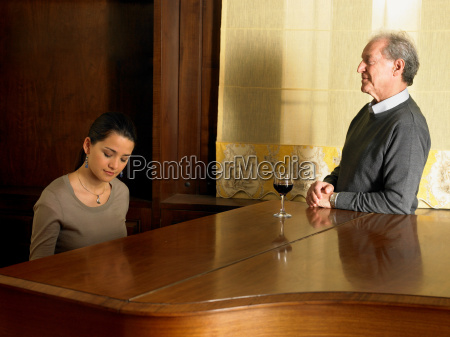 father watching daughter playing piano