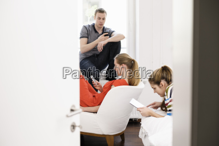 three young adult friends using mobiles
