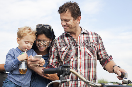 family looking at smartphone and having