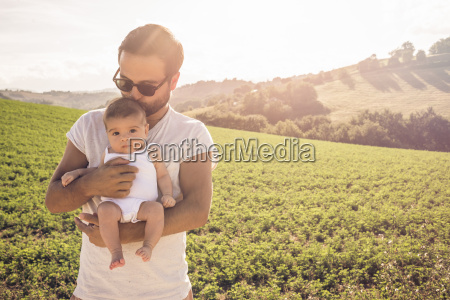 portrait of proud father holding up