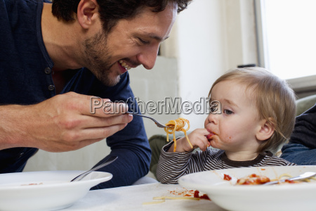 father feeding one year old daughter