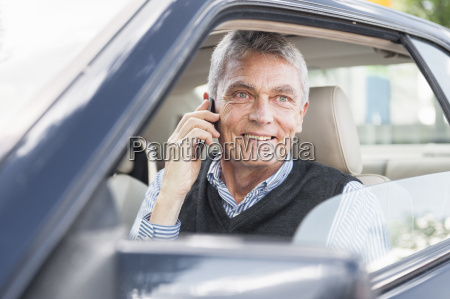 senior adult businessman in car using