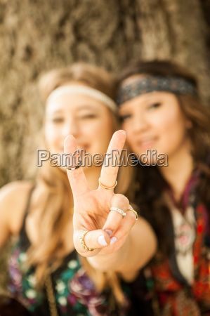 hippy women showing peace sign