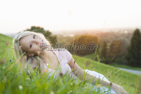 young woman lying on park hill