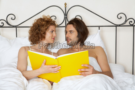 young couple in bed holding yellow