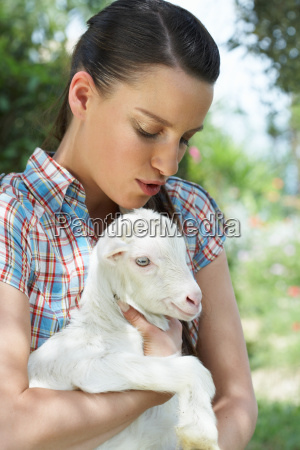young girl with goat in arm