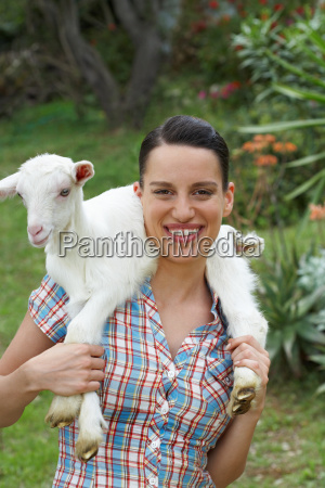 young girl with goat on shoulders