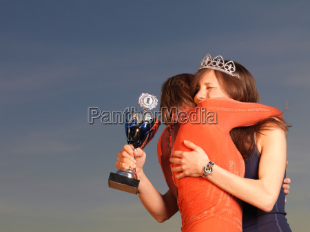 woman hugging woman holding trophy