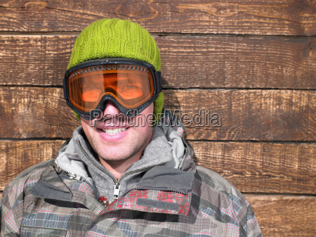 young man in goggles and snow