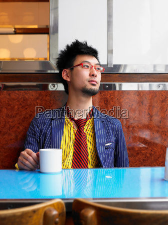young man sitting in cafe holding