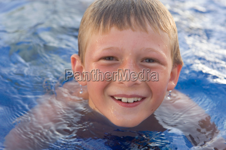 young boy smiling in swimming pool