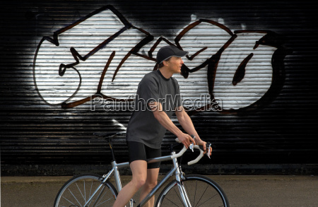 man on bicycle by graffiti in