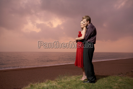 couple standing by a beach at