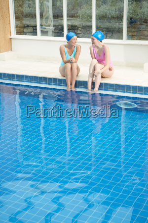 two woman by edge of swimming