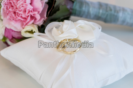 white cushion with two golden wedding