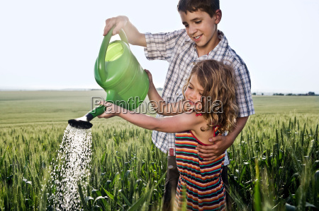boy helping girl with watering can