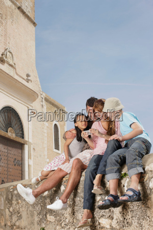 family sitting on wall sharing photos