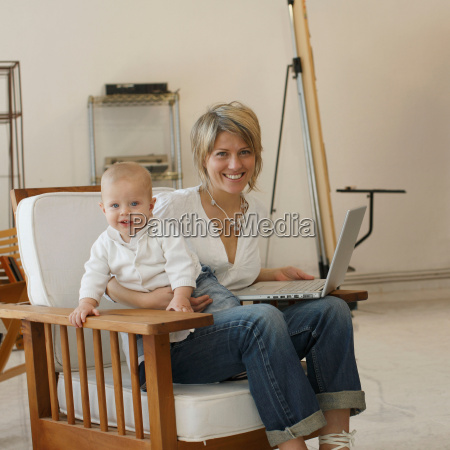 mother sitting at laptop with young