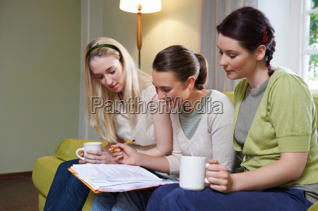 three young women sitting on couch
