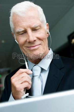 older man listening wearing head phones