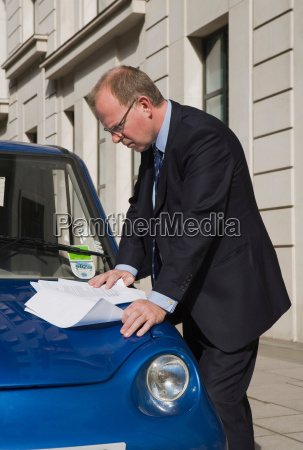 man looking at papers on car