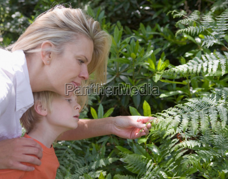 mother and son looking at fern